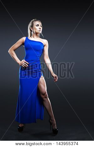Fashion portrait of beautiful woman in long dark blue dress over dark background.