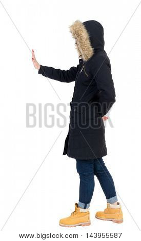 back view of woman. Young woman presses down on something. Isolated over white background. Rear view people collection. backside view of person. Girl in warm winter black jacket stands sideways and