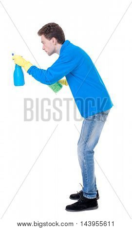 side view of a cleaner man in gloves with sponge and detergent. girl  watching.  view of person.  Isolated over white background. Curly boy in a warm blue sweater in the process of cleaning a side