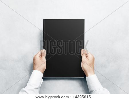 Hand holding black magazine with blank cover mockup. Arm in shirt hold journal clear template mock up. A4 book softcover surface design. Paperback print display show. Closed notebook cover showing.