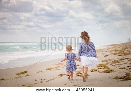 Two little siblings girls running on the ocean beach on a cloudy day. Vacation by the sea. Cute kid girl and toddler sister on the beach. outdoors. Wind in the hair of a small girls. Beach landscape