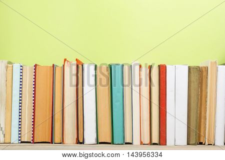 Colorful composition with vintage old hardback books, diary on wooden deck table and green background. Books stacking. Back to school. Copy Space. Education background