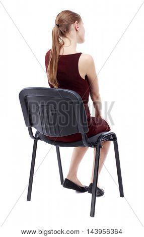 back view of young beautiful  woman sitting on chair.  girl  watching. Rear view people collection.  backside view of person.  Isolated over white background. A girl in a burgundy dress sitting on a