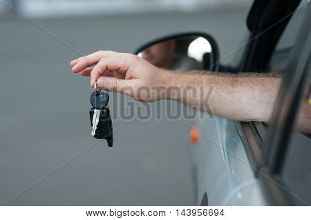 Men's hand holding a key from the car, symbolize joy purchase transport, crediting, driving. Buying a car.
