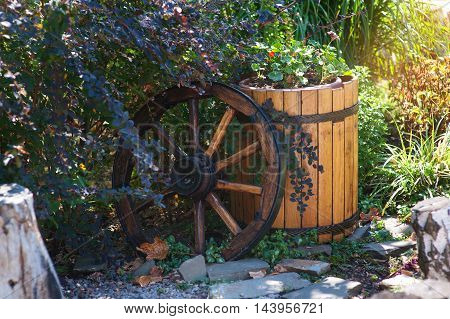 wooden wheel and barrel in the garden as decorative elements.