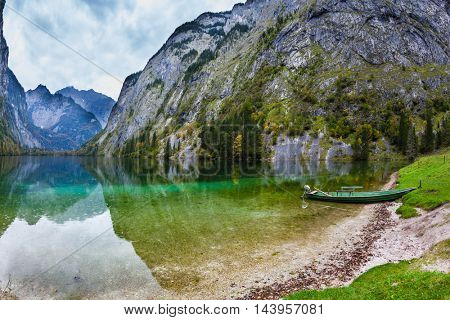 Fishing boat with a small engine in shallows of the lake. The magic blue lake Obersee in Bavarian Alps. Concept of active tourism and ecological tourism