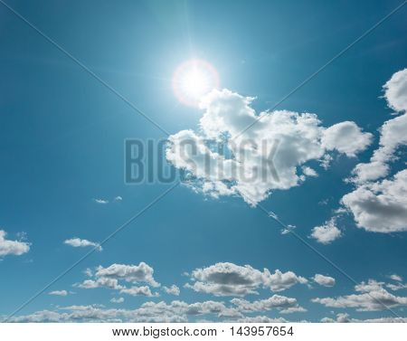 Clear blue sky with clouds and sun flare