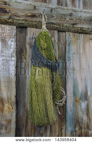 Knitted hands a fishing net on a wooden wall