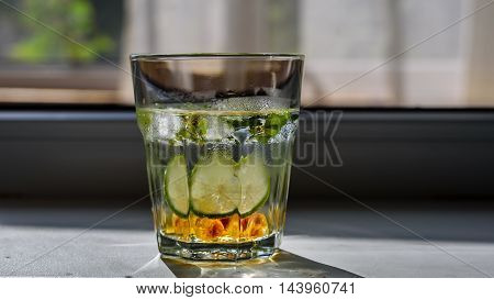 Misted glass of homemade lemonade with a slice of lime, mint leaves, sugar and ice