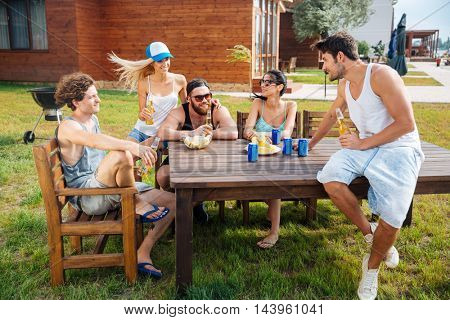 Group of happy young people sitting at the table and drinking beer outdoors