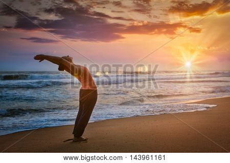 Young sporty fit man doing yoga Sun salutation Surya Namaskar pose Hasta Uttanasana on tropical beach on sunset. With lens flare