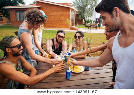 Group of happy young friends sitting and celebrating outdoors