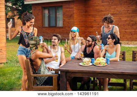 Group of happy young people celebrating and having party at the table outdoors