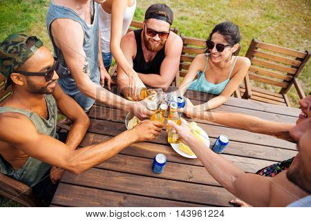 Top view of happy young friends sitting and celebrating on outdoor party
