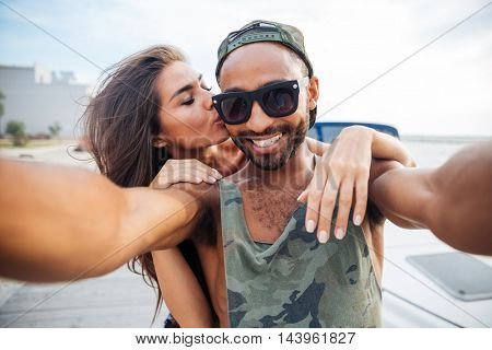 Portrait of a smiling man and woman making selfie photo on smartphone outdoors at the wooden pier