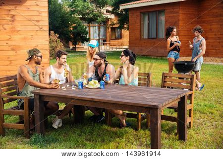 Group of smiling young friends sitting and talking on outdoor summer party