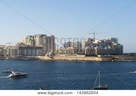 Sliema, Malta - August 02 2016: Modern Sliema skyline at Tigne Seafront. Modern apartment blocks and Tigne point bridge on Sliema's coastline.