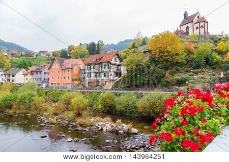 Autumn city landscape with blossoming geranium on Murg river bridge in Gernsbach, Germany