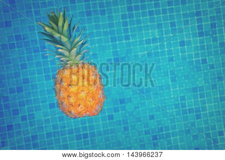 Pineapple floating in water of tiled pool, retro toned
