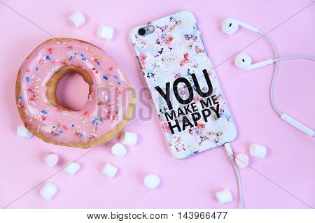 Sweet flat lay in pink with glazed donut marshmallows and mobile phone.