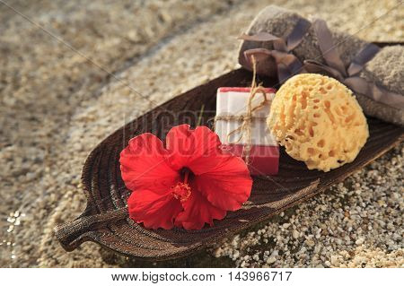 Spa and wellness setting on the seaside with natural soap tropical flower and towel.