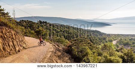 Mountain biker looking at view riding on bike in autumn inspirational mountains landscape. Man cycling biking on dirt road. Sport fitness motivation and inspiration MTB rider training Croatia.