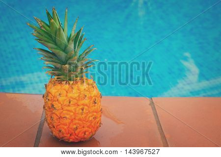 Raw whole yellow pineapple and tiled pool, retro toned
