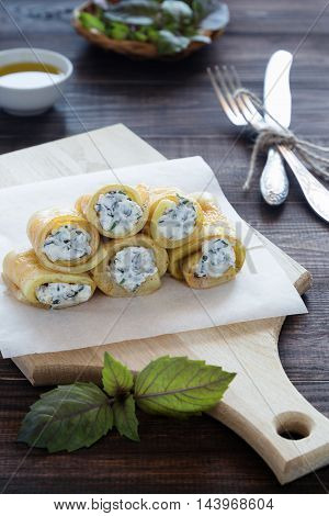 A photo of fried vegetable rolls filled with cream cheese on a cutting board