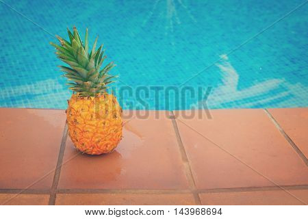 Raw whole yellow pineapple and tiled pool with blue water, retro toned