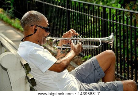 New York City - July 21 2012: Musician sitting on a bench playing a trumpet in Riverside Park