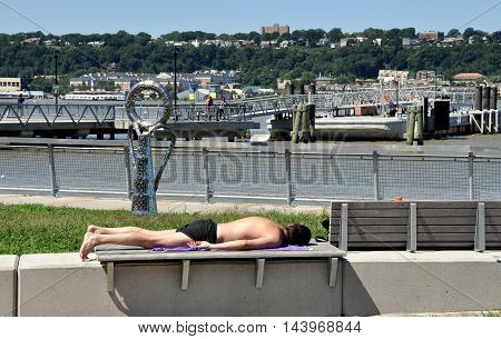 New York City - August 29 2011: Man sunbathing on a bench in Hudson River Park North at West 125th Street