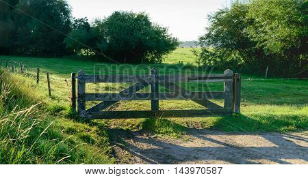 Picturesque image of a wooden gate in a Dutch agricultural landscape at low oblique sunlight early in the morning of a sunny day in the summer season.