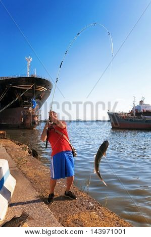 A driving boy fishing tear without bait. On the dock of an industrial harbor the fisherman, with his fishing pole, pulls out of the water a big mullet fish.