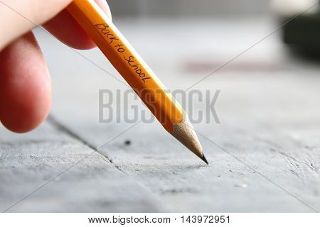 hand holding a pencil, Back to School - written in pencil