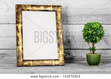 blank picture frame with artificial plant on old wood
