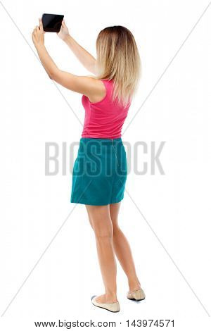 back view of standing young beautiful  woman  using a mobile phone. girl  watching. Rear view people collection.  backside view of person.  Isolated over white background. Blonde in a red sweater and