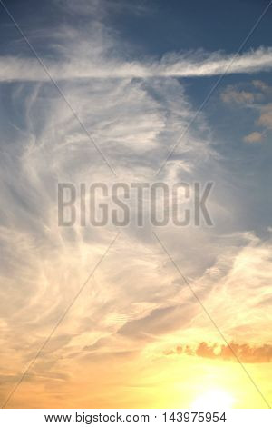 Beautiful colorful celestial sunset with white clouds high in the stratosphere in the evening vertical view