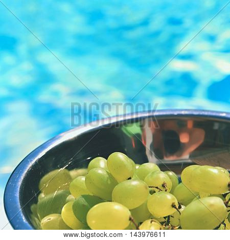 grapes in a bowl with a background of blue water