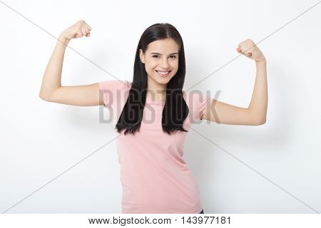 Strong woman. Beautiful young woman showing her muscularity and looking at camera while isolated on white