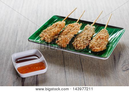 Fried chicken skewers on a green plateSpicy sauce and soy sauce