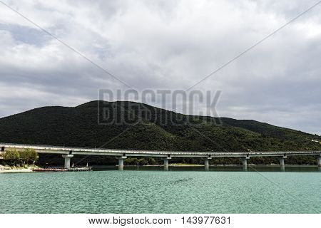 cement bridge across a lake cloudy sky