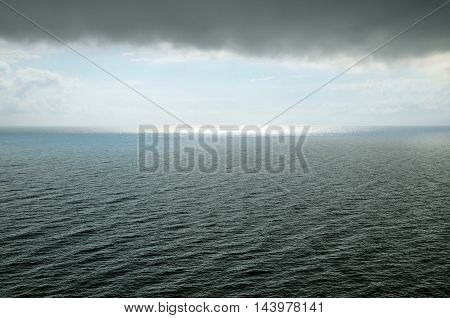 Black sea during a storm. A cloud hangs over water with waves sunlight away.