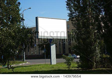 Blank billboard on a street near the road in summertime