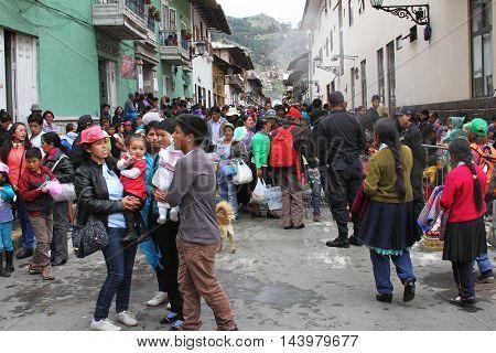 Cajamarca Peru - February 7 2016: Large group of spectators wait in street between buildings for Carnival parade in Cajamarca Peru on February 7 2016