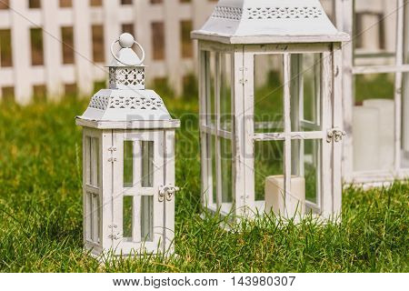Three decorative lanterns on the grass near arch for wedding ceremony