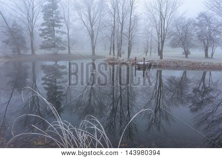 A quiet little pond on a foggy and frosty late autumn morning in southwestern Ohio near Cincinnati USA