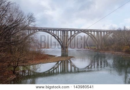 The Symmetrical Reflection of a Roadway Bridge on a Misty Late Autumn Morning Over The Little Miami River in Southwestern Ohio USA