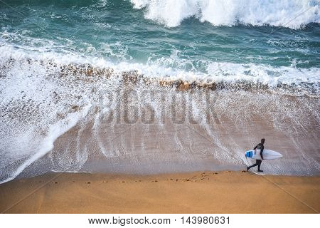 surfer man on the beach with turquoise-white water wave in the sea from top view at Bells beach Torquay Australia.