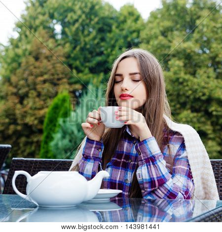 Young beautiful woman sitting at a table in outdoor cafe inhales aroma of tea