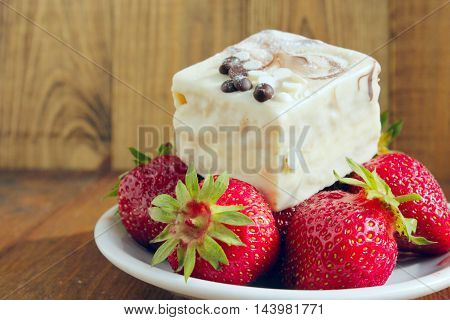 ripe strawberries and sweet cake on the white plate